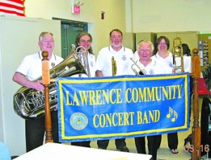 Lawrence band members around band banner